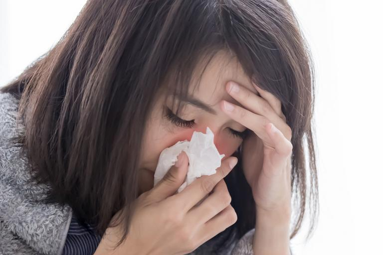 a stressed woman sneezing into a tissue